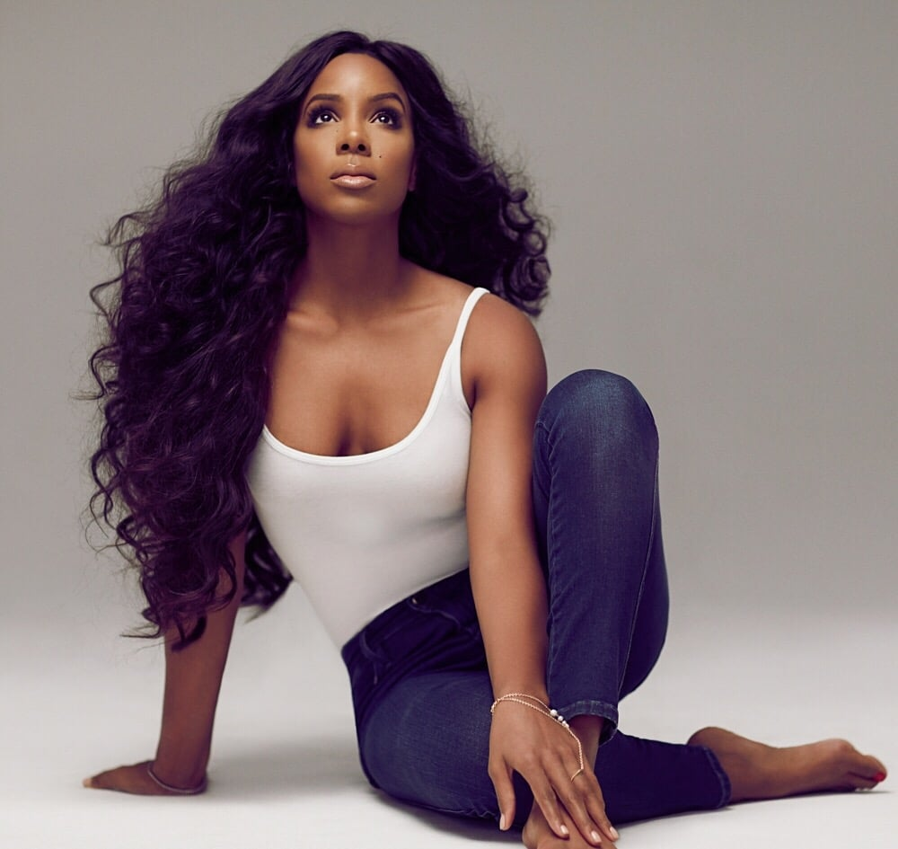 Kelly Rowland in jeans and white top modeling